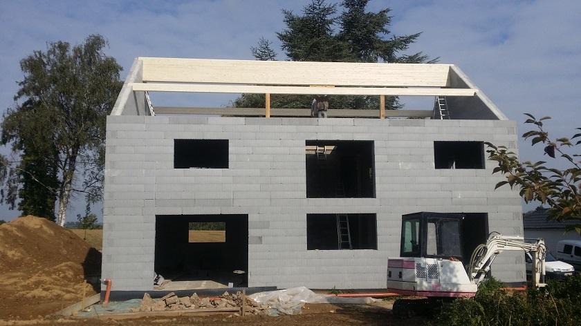 """Pose de nos poutres de support pour la toiture en bois """"lamellé-collé"""", un matériau très résistant qui permet la réalisation d'une structure de grande dimension."""